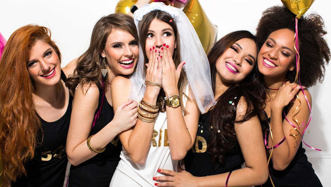 Young girlfriends celebrating bride night. Bride is wearing a veil and a T-shirt with the inscription ''BRIDE'', bridesmaids are wearing T-shirt with the inscription ''Squad''. They are laughing, dancing and singing.  Room is decorated with star and heart shaped balloons.