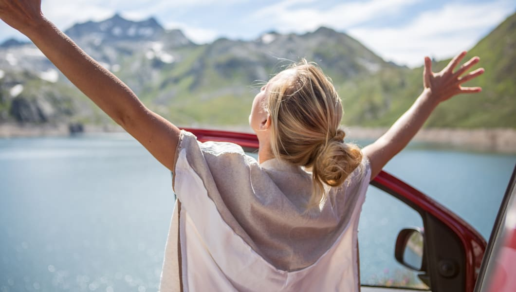 Young woman on a road trip in Switzerland enjoying the nature, arms outstretched for freedom and positive emotions. Sunny day in Summer.