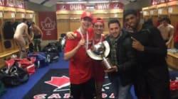 Alexandre Bilodeau se fait photographier avec les champions du monde de hockey junior... tout