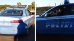Nomadi sfrecciano sull'auto della polizia nel campo rom