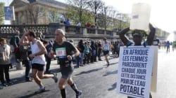 Une Gambienne au départ du marathon de Paris un bidon d'eau sur la