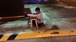 Il bambino fa i compiti alla luce del