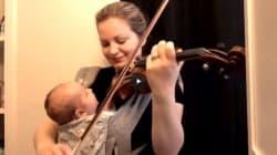 Suona il violino con il bambino in braccio: