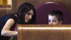Raggi prende in braccio il figlio di 7 anni e lo fa sedere sullo scranno da
