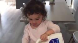 Cette fillette tente de se verser un verre de lait toute seule et c'est