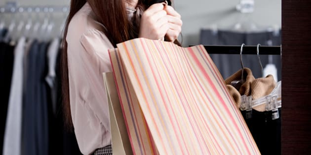woman carries paper bags after...