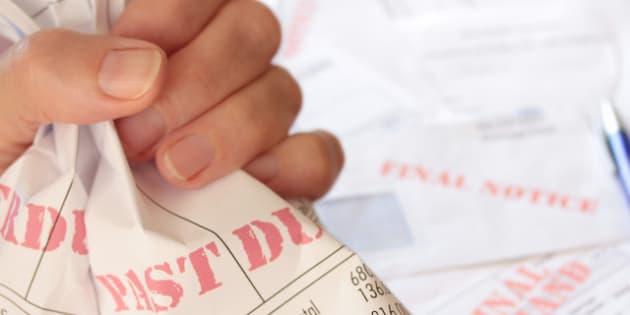 unpaid bills clutched in hand