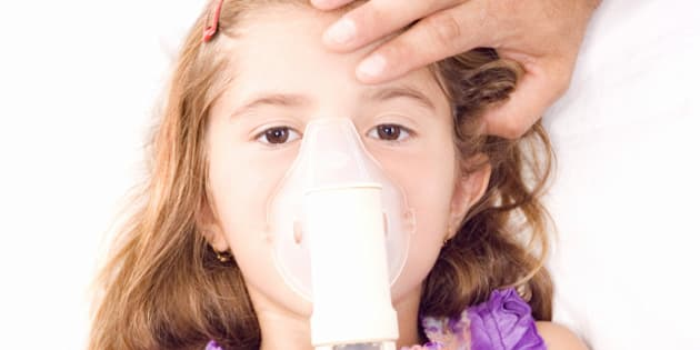 little girl inhaling medicine