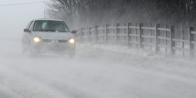 Vehicles drive through drifting snow on the A6 road near the town of Buxton in north-west England, on March 22, 2013. Britain should be celebrating the start of spring but the kingdom was shivering Friday after heavy snowfall left tens of thousands of homes without power. AFP PHOTO / ANDREW YATES        (Photo credit should read ANDREW YATES/AFP/Getty Images)