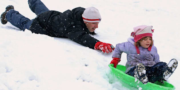 TAKOMA PARK, MD - MARCH 25:  Chris Myers Asch gives his daughter Miriam Asch, 5, a little push down a hill at Takoma Park Middle School as a wet and heavy snow falls March 25, 2013 in Takoma Park, Maryland. An early-spring snow blanketed parts of the nation's capital less than a week before the Easter holiday.  (Photo by Chip Somodevilla/Getty Images)