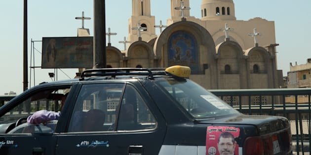 TO GO WITH AFP STORY BY MONA SALEM- A Cairo cab bearing a portrait of  Egypt's newly elected President Mohamed Morsi drives past a Coptic church in the Egyptian capital on June 25, 2012. Many Coptic Christians had feared a win by the Islamist as they had witnessed an increase in sectarian attacks since the overthrow of president Hosni Mubarak early last year. AFP PHOTO / KHALED DESOUKI        (Photo credit should read KHALED DESOUKI/AFP/GettyImages)