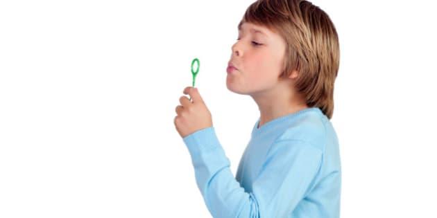adorable preteen boy blowing...