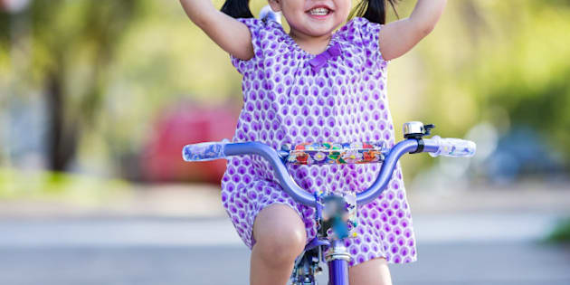 Little girl riding and smiling with her fingers held up high.