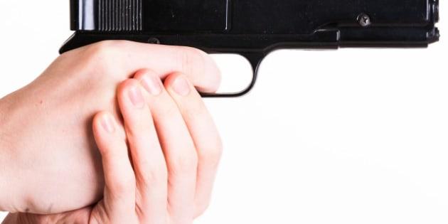 teen holds a handgun on white...