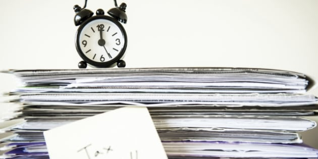 Traditional alarm clock on top of a stack of paper documents.