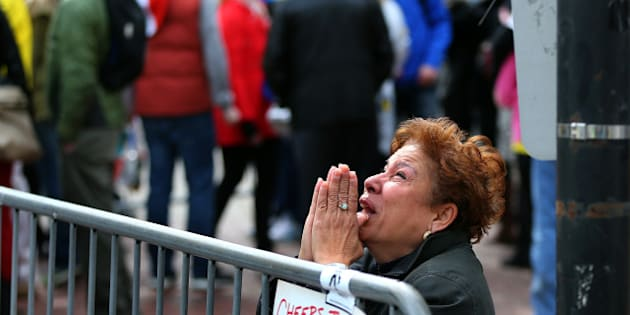 BOSTON - APRIL 15: A woman kneels and prays at the scene of the first explosion on Boylston Street near the finish line of the 117th Boston Marathon on April 15, 2013. (Photo by John Tlumacki/The Boston Globe via Getty Images)