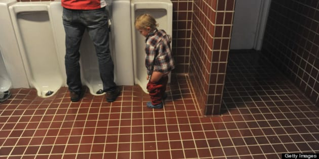Boy pulls up pants after using the urinal in tiled restroom.