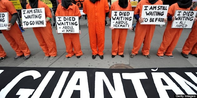 People dress in orange jumpsuits and black hoods as activists demand the closing of the US military's detention facility in Guantanamo during a protest, part of the Nationwide for Guantanamo Day of Action, April 11, 2013 in New York's Times Square. The Guantanamo jail, in a US Navy base in Cuba, was opened in 2002 to hold prisoners taken in the 'War on Terror' waged by then US President George W. Bush after the 9/11 attacks. AFP PHOTO/Stan HONDA        (Photo credit should read STAN HONDA/AFP/Getty Images)
