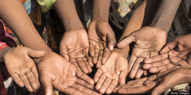 Poor children in Ethiopia with outstretched hands asking for money. Some unrecognizable persons.