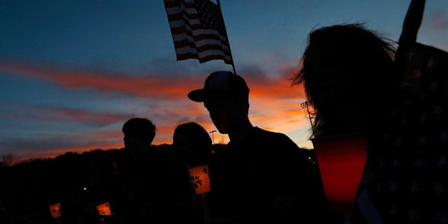 WATERTOWN, MA - APRIL 20: Residents of Watertown stand during a moment of silence at a candlelight vigil at Victory Park on April 20, 2013 in Watertown, Massachusetts. A manhunt for Dzhokhar A. Tsarnaev, 19, a suspect in the Boston Marathon bombing ended after he was apprehended on a boat parked on a residential property in Watertown, Massachusetts. His brother Tamerlan Tsarnaev, 26, the other suspect, was shot and killed after a car chase and shootout with police. The bombing, on April 15 at the finish line of the marathon, killed three people and wounded at least 170.  (Photo by Jared Wickerham/Getty Images)