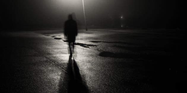 A shadowy figure walks through a rain soaked parking lot under a street light at night.