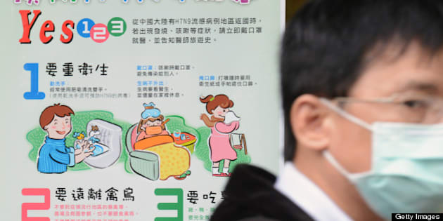 A man wearing a mask walks past a H7N9 poster outside the National Taiwan University Hospital in Taipei on April 25, 2013. International experts probing China's deadly H7N9 bird flu virus said on April 24 it was 'one of the most lethal influenza viruses' seen so far as Taiwan reported the first case outside the mainland.   AFP PHOTO / Sam Yeh        (Photo credit should read SAM YEH/AFP/Getty Images)