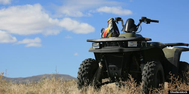 atv parked on hill with scenic...