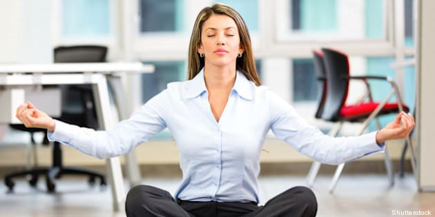 business woman doing yoga at...
