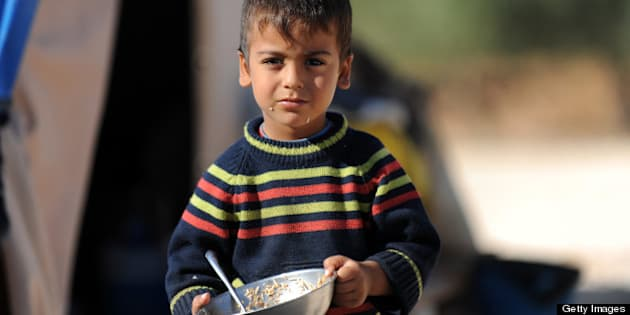 A Syrian boy looks on as he holds his plate of food in a newly built refugee camp at the village of Qah, northwestern Idlib, near the Turkish border, on October 14, 2012, which is under the control of rebel fighters. Hundreds of Syrian displaced families who were settled in a makeshift camp along the Turkish border, have been transfered to the Qah Camp, the first formal camp inside Syria, which is intended to accommodate up to 5000 refugees. AFP PHOTO/BULENT KILIC        (Photo credit should read BULENT KILIC/AFP/GettyImages)