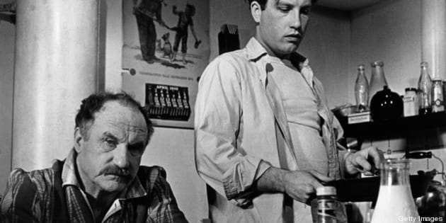 Jack Warden sitting at a dining table while Richard Dreyfuss is standing beside him holding a pan in a scene from the film 'The Apprenticeship of Duddy Kravitz', 1974. (Photo by Paramount Pictures/Getty Images)