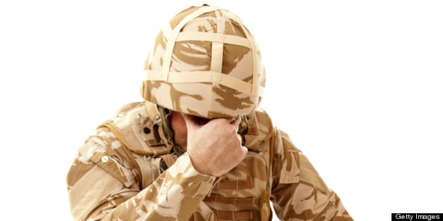 A distraught soldier on one knee with one hand covering his face, possibly suffering from shell shock or Post Traumatic Stress Disorder
