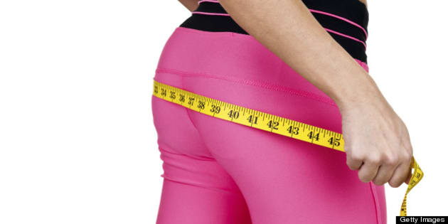 Woman wearing fitness clothing measuring her buttocks for a fitness and weight loss concept