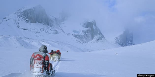 Inuit snowmobiles pull expedition members across a frozen lake.