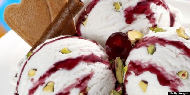 Vanilla ice cream balls with cherry syrup and pieces of pistachio