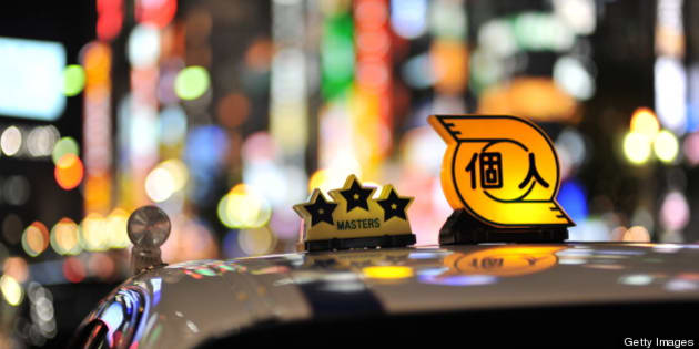 [UNVERIFIED CONTENT] A taxi in shinjyuku tokyo. The background are the buildings lining the kabukicho area. Extremely colourful lights. Taxi top. Three stars and private taxi. White taxi at night.  out of focus bokeh nightlife
