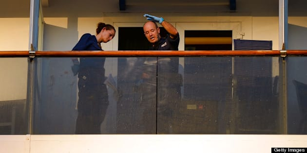 Two police officers check for fingerprints on the balcony of the cabin of two passengers who fell overboard from the cuise ship Carnival Spirit as it returned to Sydney from a Pacific cruise, on May 9, 2013.  A search was underway off Australia for the couple in shark-infested waters and after reviewing security footage on the ship, police said they believe the pair fell overboard just before 9pm on Wednesday (1100 GMT Wednesday) around 65 nautical miles off the coast, north of Sydney.  AFP PHOTO / William WEST        (Photo credit should read WILLIAM WEST/AFP/Getty Images)