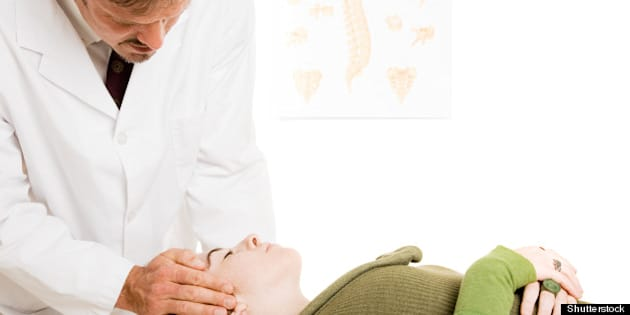 chiropractor gently adjusting a ...