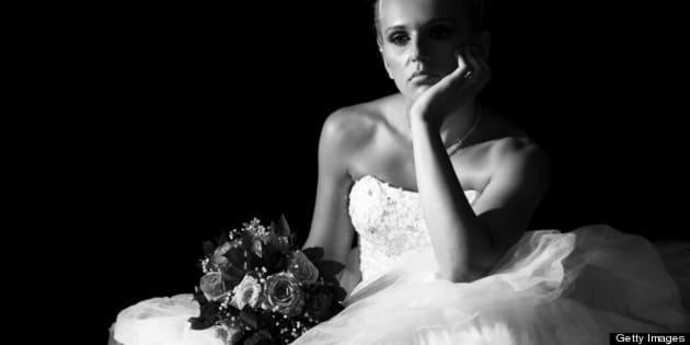 Sad bride sitting in the dark. Black and white.