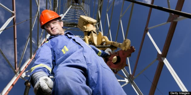 A royalty free image from the oil industry of an oil worker at a oil well.