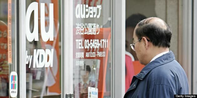 TOKYO, JAPAN:  A man enter a mobile phone shop of 'au', mobile service brand of Japan's number two telecoms operator KDDI, in Tokyo, 27 January 2005. KDDI's net profit in the nine months to December jumped 24.9 percent to 154.1 billion yen (1.5 billion dollars) on robust demand for mobile phone services.       AFP PHOTO/Toru YAMANAKA  (Photo credit should read TORU YAMANAKA/AFP/Getty Images)