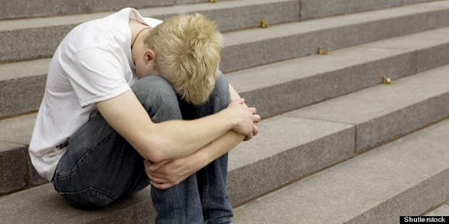 upset young blond man sitting...