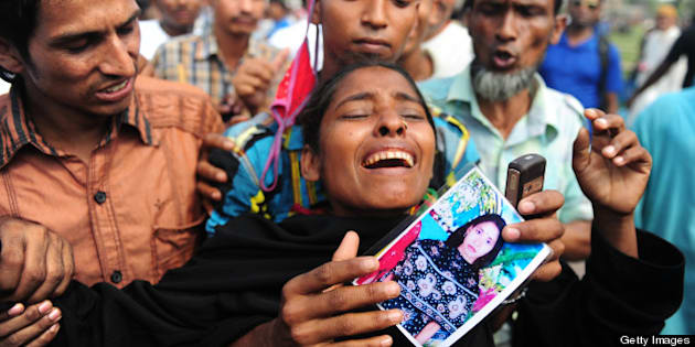 A relative of a missing Bangladeshi garment worker reacts as she gathers at a graveyard for victims of the garment factory collapse in Dhaka on May 1, 2013. Tens of thousands of Bangladeshis joined May Day protests Wednesday to demand the execution of textile bosses over the collapse of a factory complex, as rescuers warned the final toll could be more than 500. AFP PHOTO/Munir uz ZAMAN        (Photo credit should read MUNIR UZ ZAMAN/AFP/Getty Images)