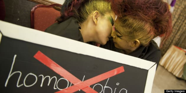 A lesbian couple kisses behind a placard reading 'Homophobia' as they take part in an event to celebrate the International day against Homophobia and Transphobia on May 17, 2013, in Yangon.  AFP PHOTO / YE AUNG THU        (Photo credit should read Ye Aung Thu/AFP/Getty Images)