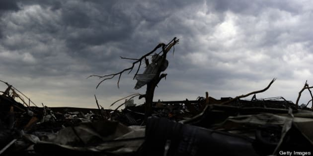 Rain clouds roil over a tornado devastated neighborhood on May 23, 2013 in Moore, Oklahoma. Severe thunderstorms barreled through this Oklahoma City suburb at dawn Thursday, complicating clean-up efforts three days after a powerful tornado killed 24 people and destroyed 2,400 homes. More rain was forecast to fall on Moore, soaking the disaster zone where residents had just the day before, under clear blue skies, started picking through the rubble of their destroyed houses to recover personal effects. AFP PHOTO/Jewel Samad        (Photo credit should read JEWEL SAMAD/AFP/Getty Images)