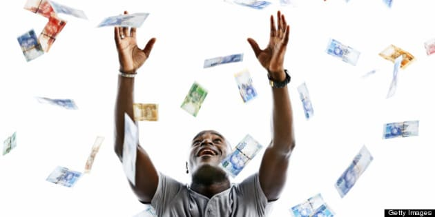 A happy man looks up smiling as he tries to catch hundreds of falling banknotes. The banknotes are varied denominations of the new South African currency featuring South African statesman, Nelson Mandela. Isolated on white.