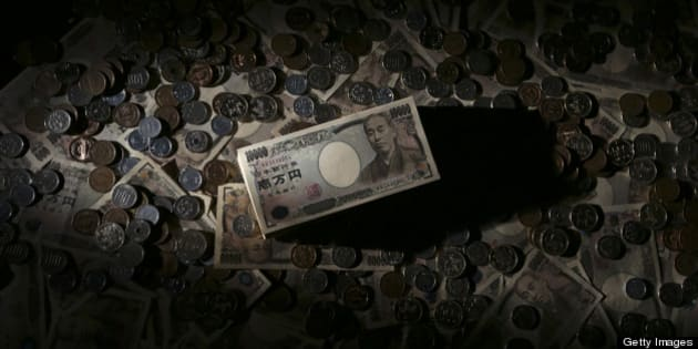 Japanese 10,000 yen banknotes and coins of various denominations are arranged for a photograph in Tokyo, Japan, on Monday, Feb. 25, 2013. The yen's protracted climb against the dollar over the past four decades is over, said Makoto Utsumi, a former top Japanese currency official. Photographer: Yuriko Nakao/Bloomberg via Getty Images