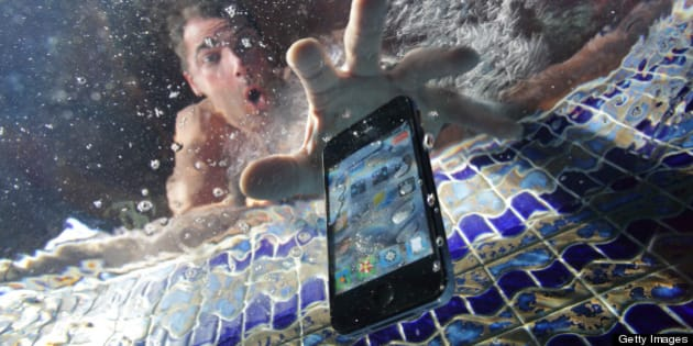 Smart phone being dropped into swimming pool
