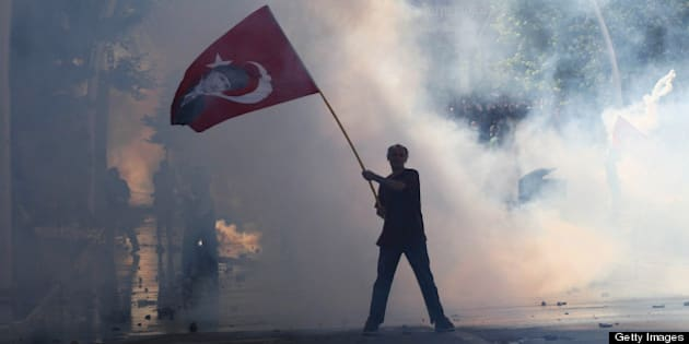 Tear gas surrounds a protestor holding a Turkish flag with a portrait of the founder of modern Turkey Mustafa Kemal Ataturk as he takes part in a demonstration in support of protests in Istanbul and against the Turkish Prime Minister and his ruling Justice and Development Party (AKP), in Ankara, on June 1, 2013. Turkish police on June 1 began pulling out of Istanbul's iconic Taksim Square, after a second day of violent clashes between protesters and police over a controversial development project. Thousands of demonstrators flooded the site as police lifted the barricades around the park and began withdrawing from the square.  What started as an outcry against a local development project has snowballed into widespread anger against what critics say is the government's increasingly conservative and authoritarian agenda. AFP PHOTO / ADEM ALTAN        (Photo credit should read ADEM ALTAN/AFP/Getty Images)