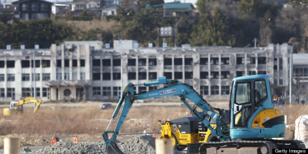 An excavator operates on a construction site as an abandoned elementary school stands in the background in an area damaged by the tsunami following the Great East Japan Earthquake in Ishinomaki, Miyagi Prefecture, Japan, on Sunday, March 10, 2013. Japan's economy grew at an annualized 0.2 percent last quarter after shrinking 3.7 percent the three previous months, the worst since the 2011 earthquake, revised government data show. Photographer: Kiyoshi Ota/Bloomberg via Getty Images