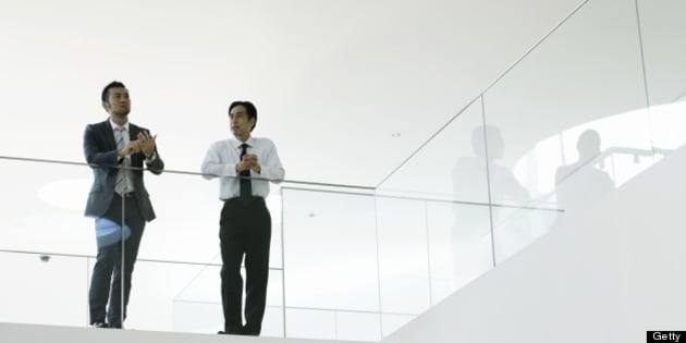 Businessman and mature businessman talking in office hallway resting arm on glass wall.Yokosuka Museum of Art,Kanagawa Prefecture,Japan.